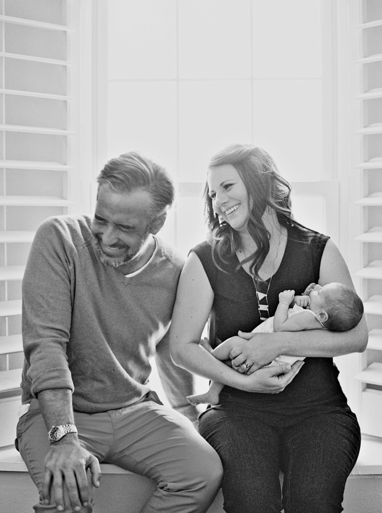 New parents laugh together as they hold their newborn baby daughter