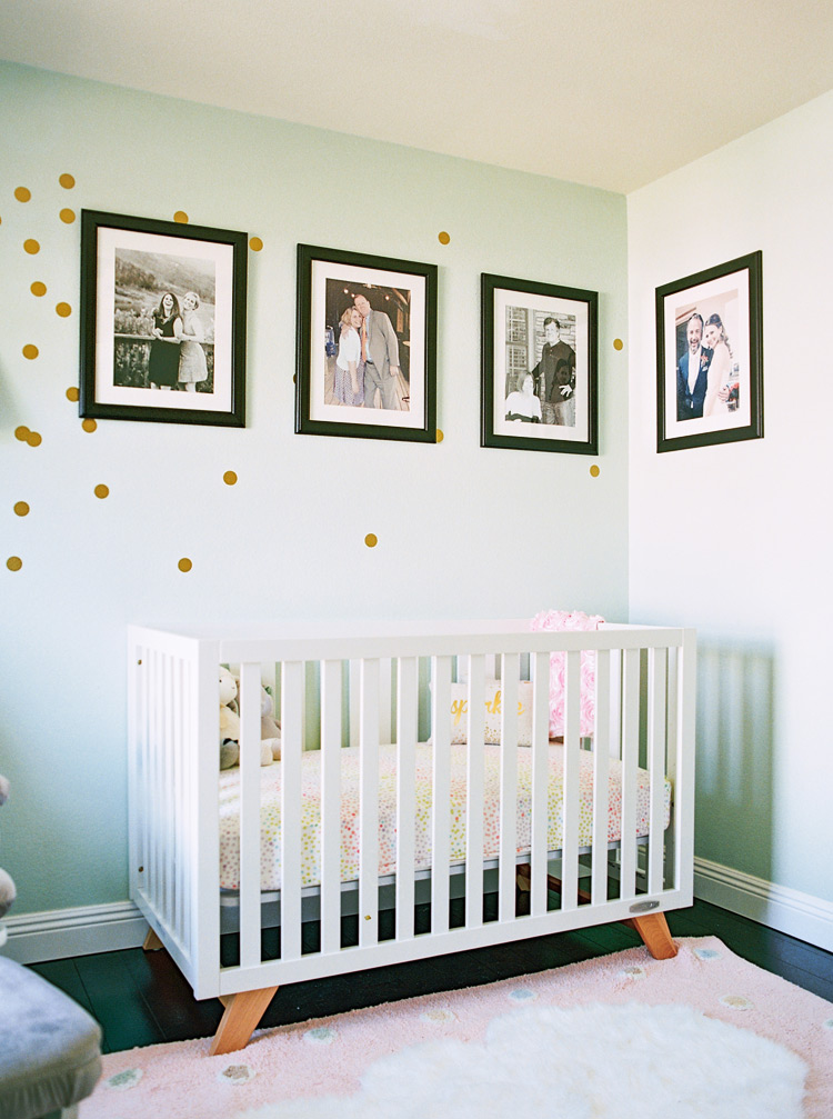 Charming pastel nursery with custom polka dots walls and family portraits