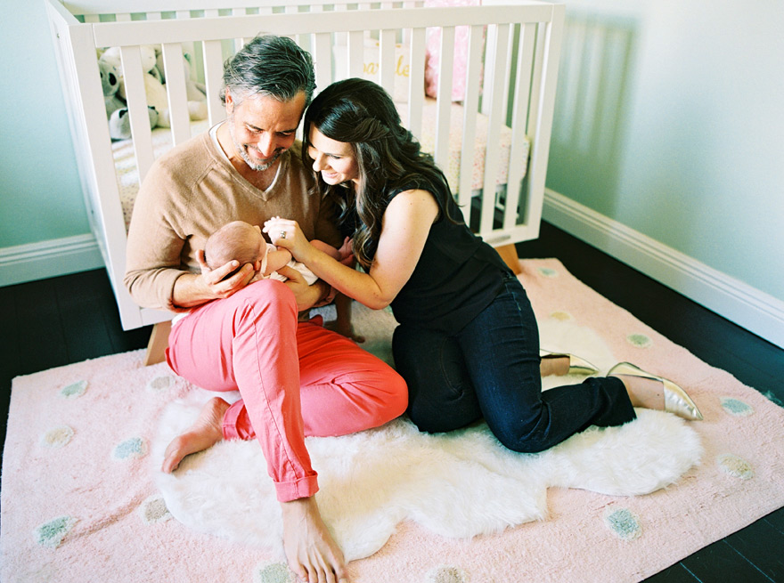 New parents sit with their newborn baby daughter in her pretty pastel nursery