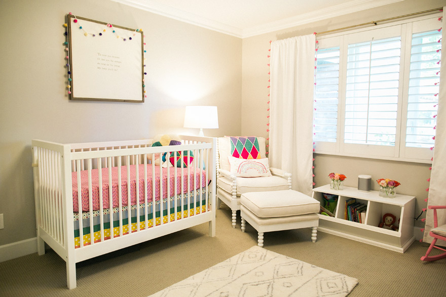 Newborn nursery with bright crib and patterned room layout.