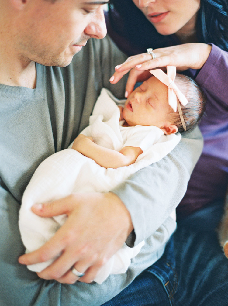 Father holding wrapped newborn baby with mother admiring new daughter.