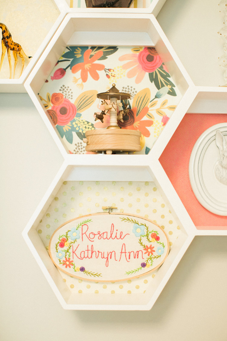 Geometric shelves with wooden carousel and embroidered name plate.
