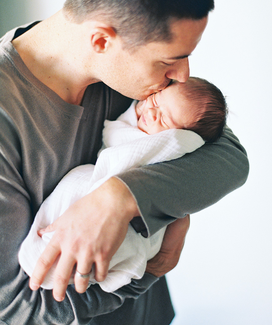 Father gently kisses sleeping baby in arms on forehead.