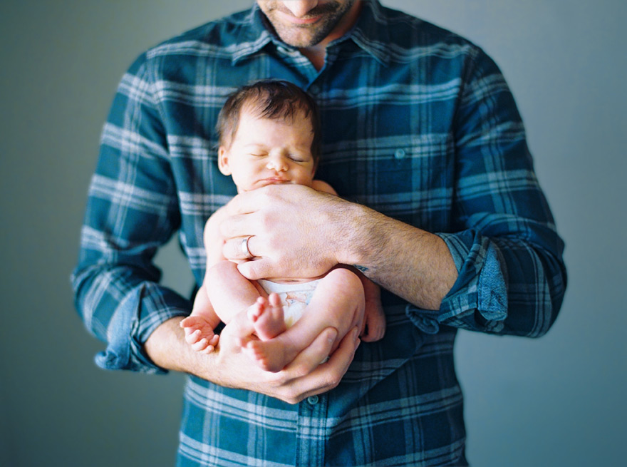 newborn baby girl held by father