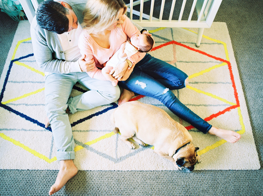 Couple cradles their newborn baby on the nursery floor.  Bold geometric rug.