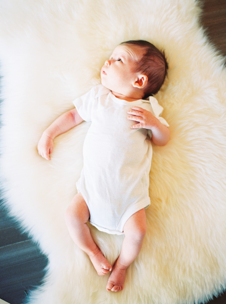 Curious newborn baby lays on a fluffy blanket.
