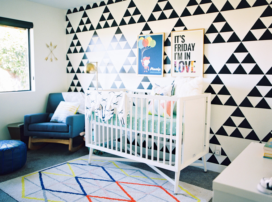 Modern nursery with bold geometric wallpaper and vibrant rug.