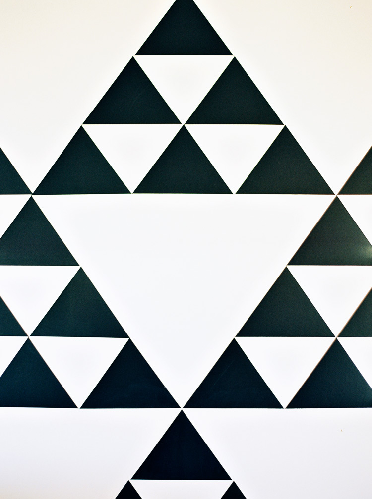 Bold geometric wallpaper with a black and white pattern of triangles.