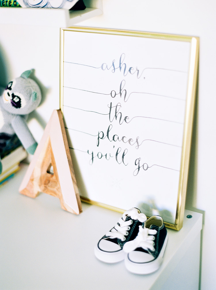 Hand-lettered calligraphy print decorating a modern nursery.