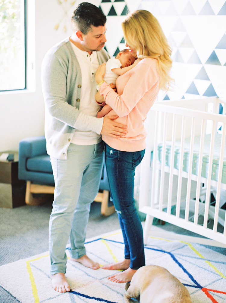 Couple cuddles their newborn baby in their modern nursery.
