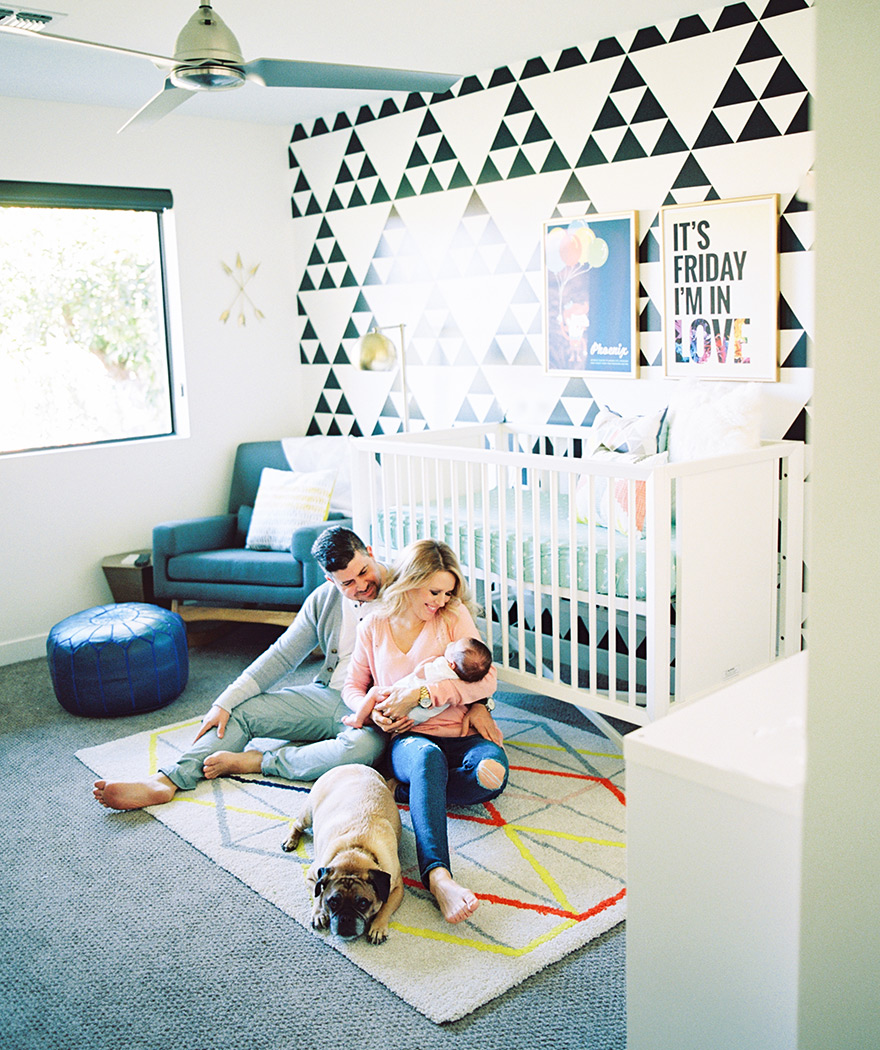 Couple cradles their newborn baby on the nursery floor.  Bold geometric rug & graphic wallpaper.