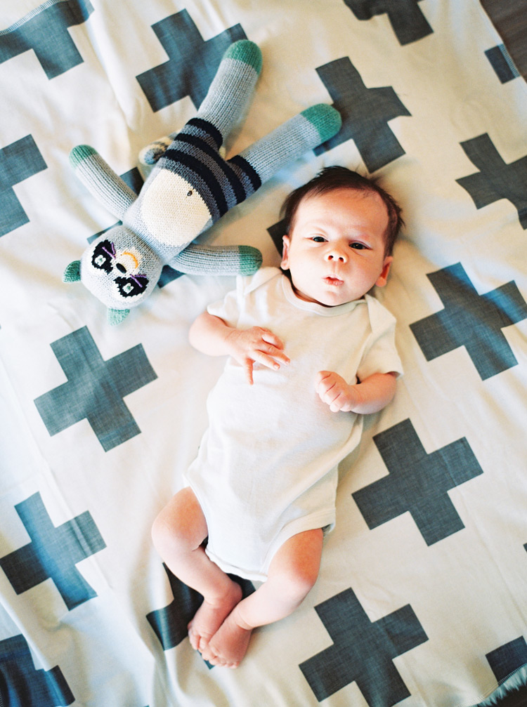 Newborn baby and his stuffed toy gaze up at the world.