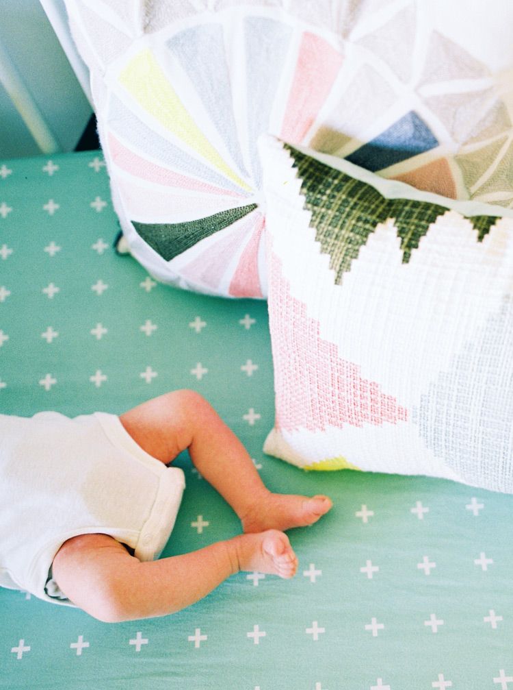 Tiny feet of a newborn baby. Decorative pillows in graphic patterns.