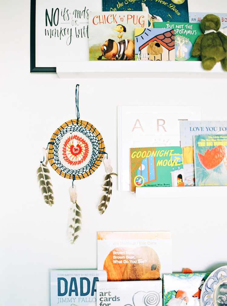 Whimsical modern nursery decor with story books and a dreamcatcher.