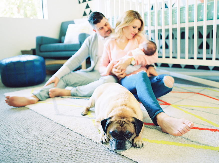Happy young family -- mom, dad, baby, and dog -- sitting on the nursery floor. Modern baby's room.