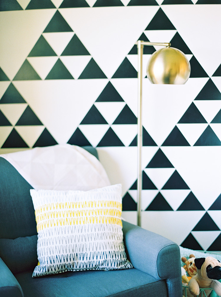 Graphic black & white wallpaper behind a comfortable seating vignette.