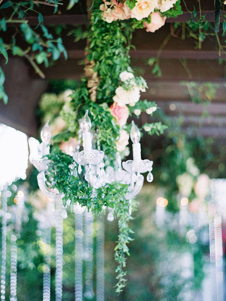 flower decked chandelier at outdoor wedding ceremony