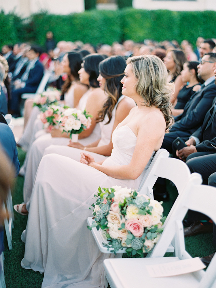 bridesmaids in palest pink at outdoor wedding ceremony