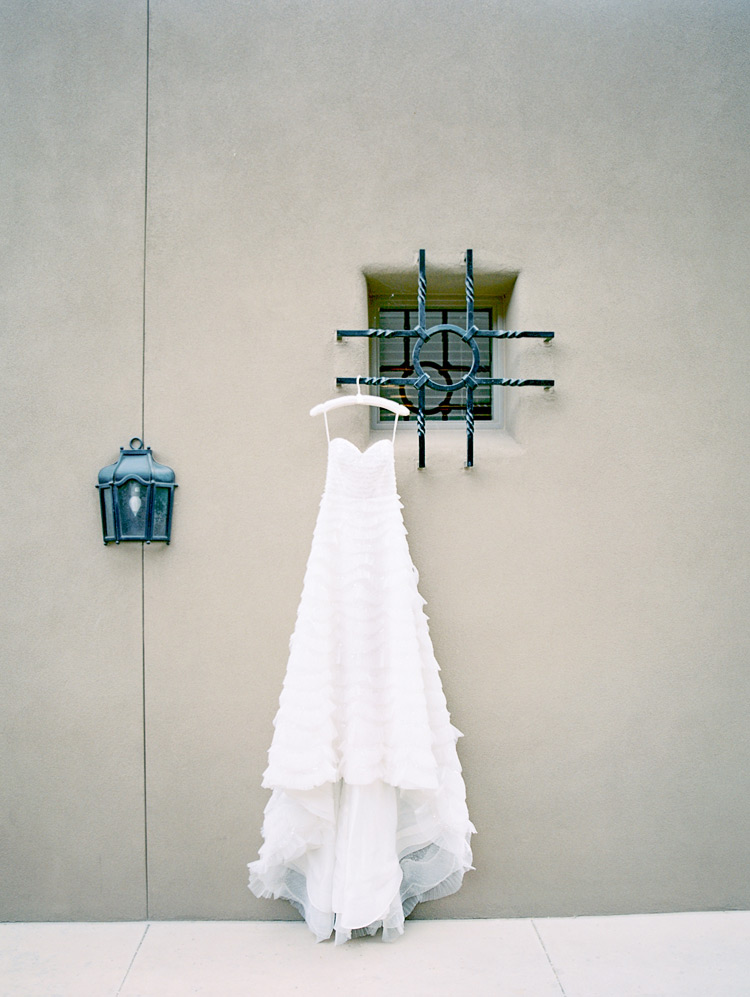 Wedding gown hanging outdoors. Long strapless A-line dress with ruffles.