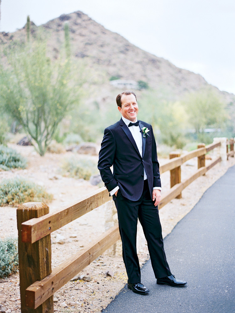 Smiling groom in a classic black tux. Desert wedding