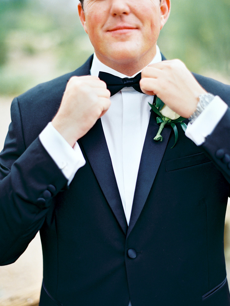 Groom's final touches! Black tux with bow tie.