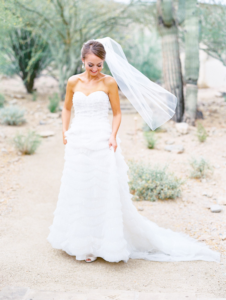 Smiling bride in a ruffled gown walks in the desert.