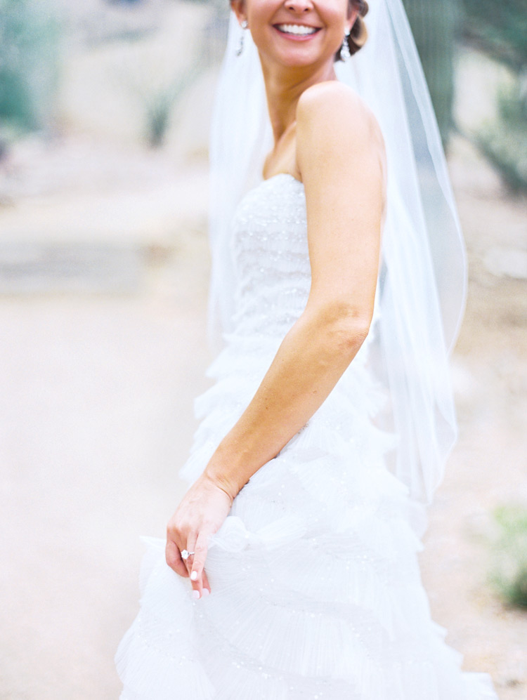 Happy bride in her sparkling, ruffled gown. Wedding style