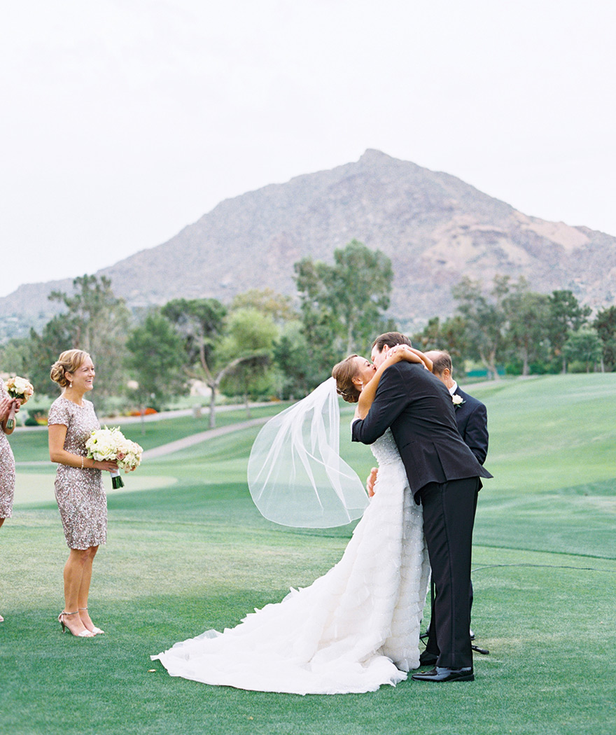 Kiss the bride! Happy moment in an outdoor wedding ceremony