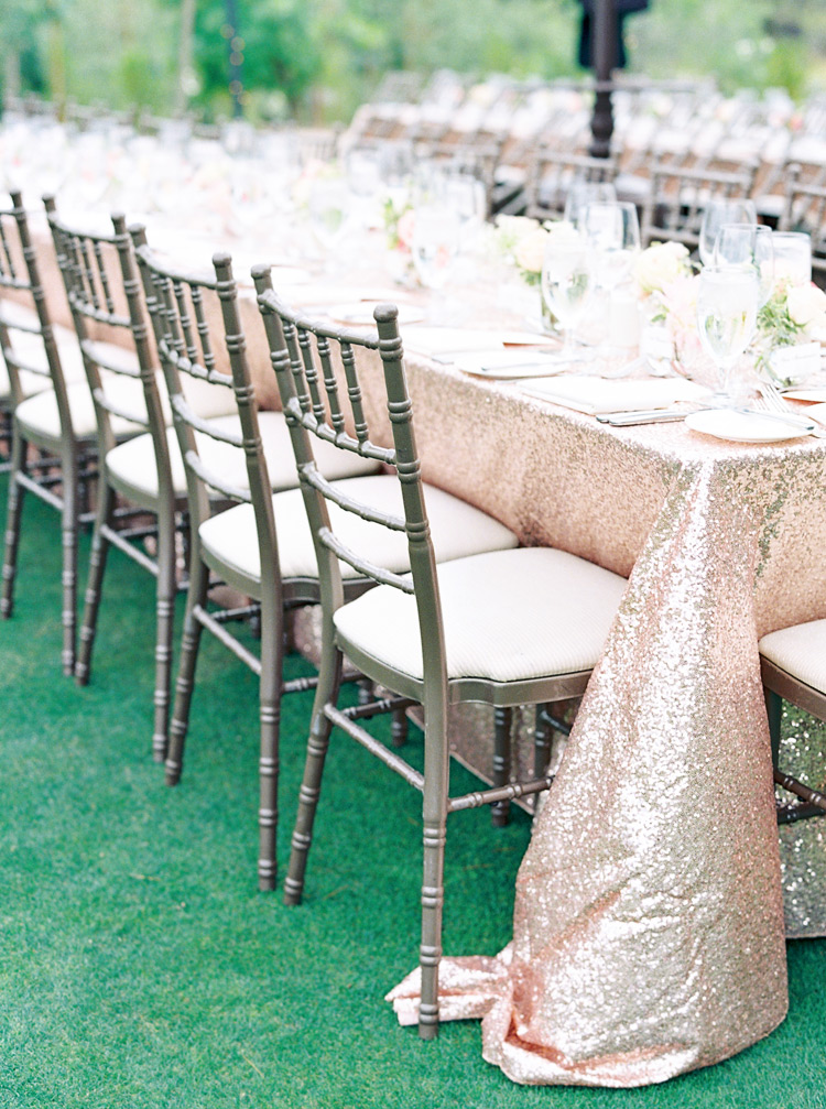 Elegant outdoor wedding reception with long tables and sequined linens