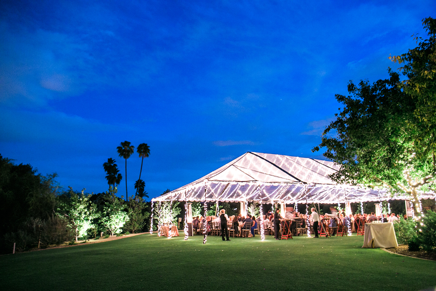 Clear tent glows with lights in the desert twilight. Outdoor wedding reception