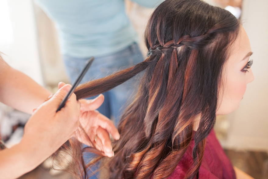 Long, dark hair being braided into an elegant waterfall braid. Bridal hair idea.