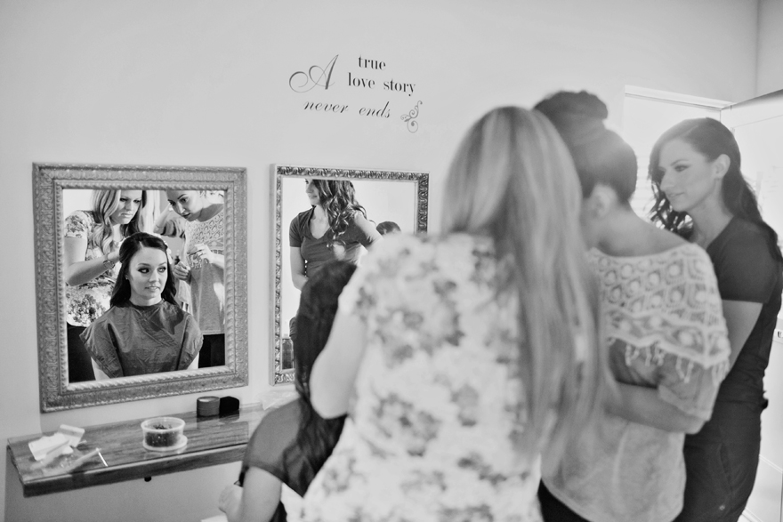 Bride having her hair done before her wedding. Bridal preparation. Black & white candid photos.