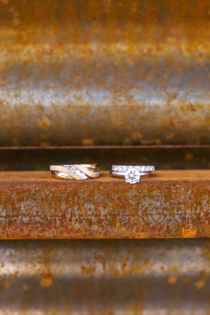 Wedding rings displayed on a rustic metal ledge. Solitaire engagement ring with diamond wedding band