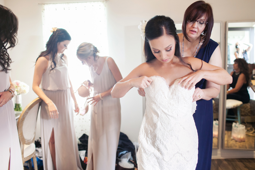 Mother of  the bride helps her daughter into her dress. Bridal preparation. Special wedding moments.