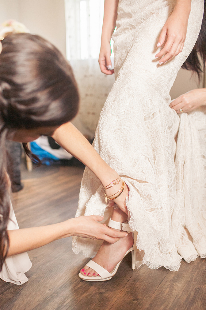 Bridesmaids help the bride with finishing touches. Bridal preparation. Lace wedding dress.