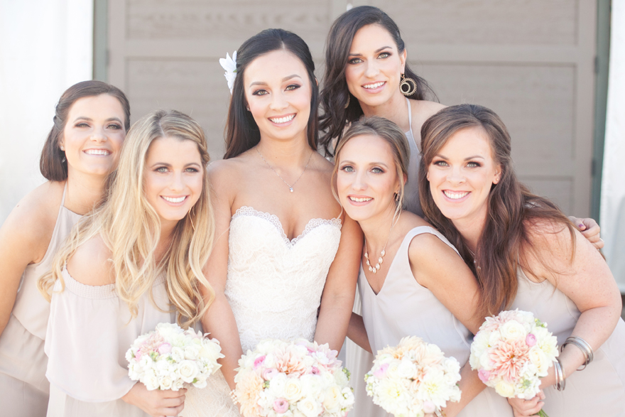 Bridesmaids surround the happy bride. Bridesmaids in matching colors but different silhouettes.