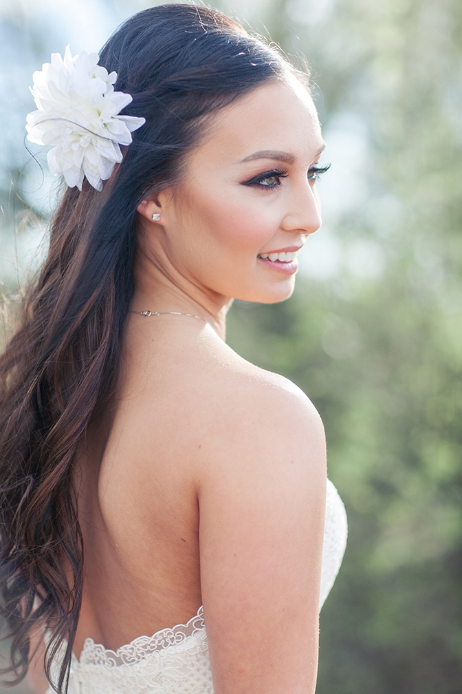 Beautiful wedding look -- bride with long, dark hair in a waterfall braid, with a flower.