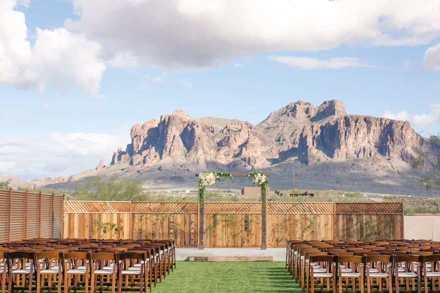 Outdoor wedding ceremony with a decorated arch and a stunning mountain view. Arizona wedding