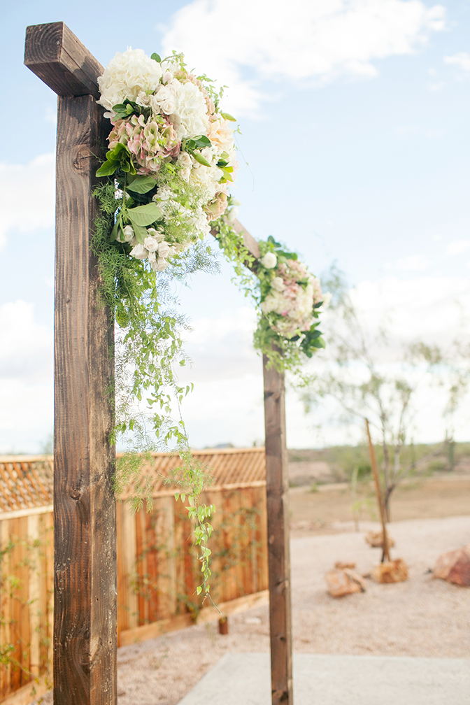 Wooden arch decorated with hydrangeas & greenery for an outdoor wedding ceremony. Arizona wedding.