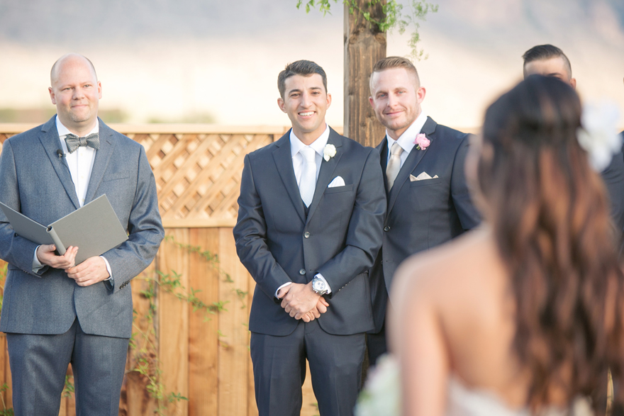 Smiling groom awaits his bride as she walks down the aisle. Outdoor Arizona wedding ceremony.