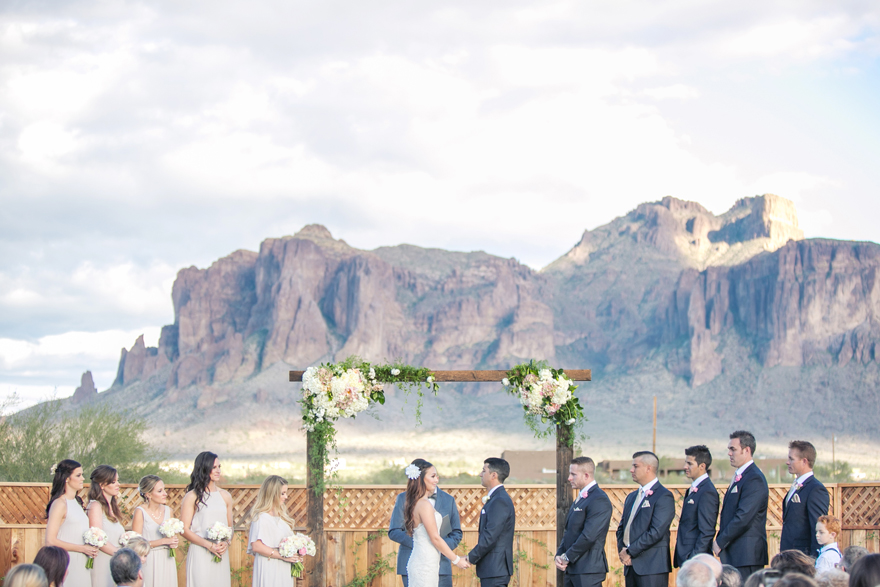 Dramatic mountain view at an outdoor wedding ceremony in Arizona. Wedding party at the altar.