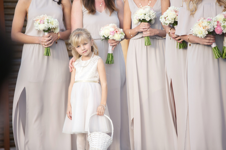 Flower girl stands with the bridesmaids during an outdoor wedding ceremony. Bridal party style.