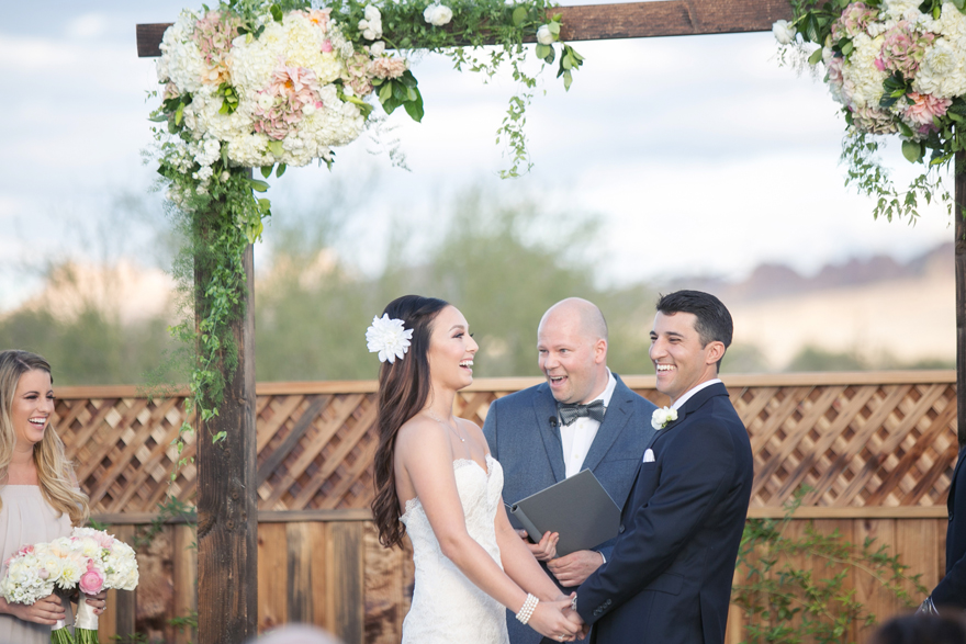 Bride & groom laugh together during their outdoor Arizona wedding ceremony. Happy wedding moments!