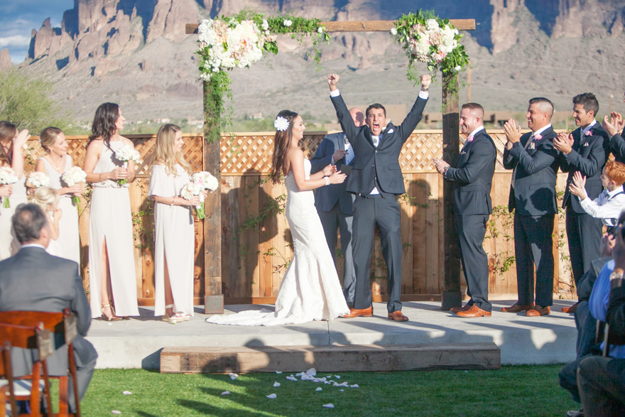 Triumphant groom celebrates at the altar. Joyous moment in an outdoor wedding ceremony.