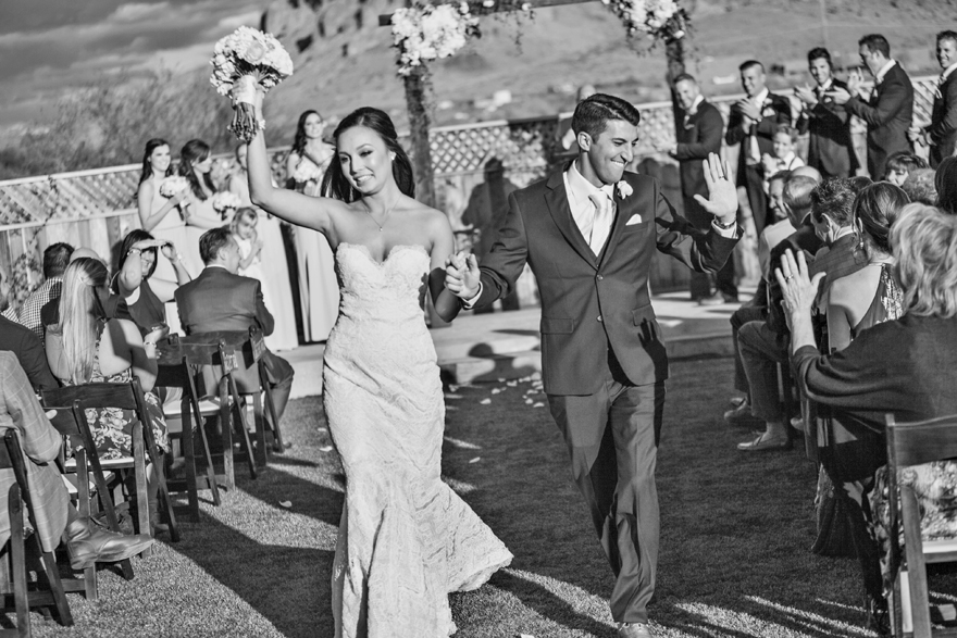 Bride & groom waves and laugh as they walk back down the aisle. Outdoor wedding ceremony recessional