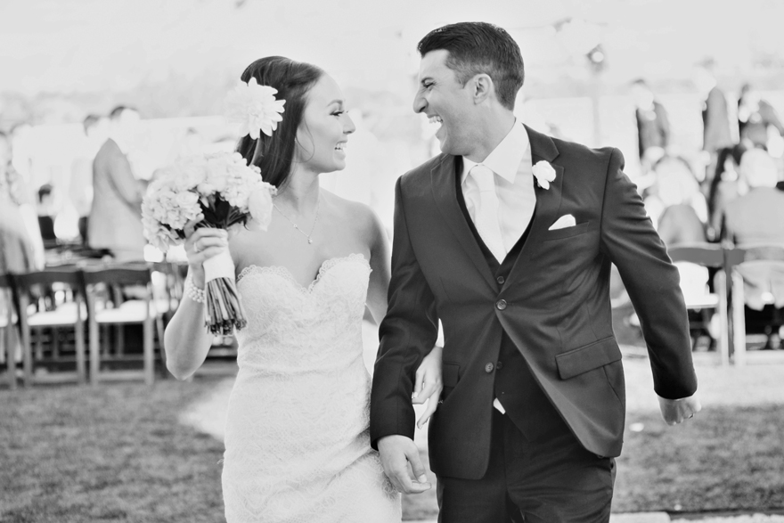 Bride & groom laugh together as they walk back down the aisle. Outdoor wedding ceremony recessional.