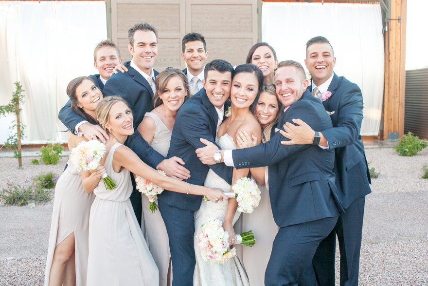 Wedding party share the joy with the bride & groom in a group hug. Happy bridal party portrait.