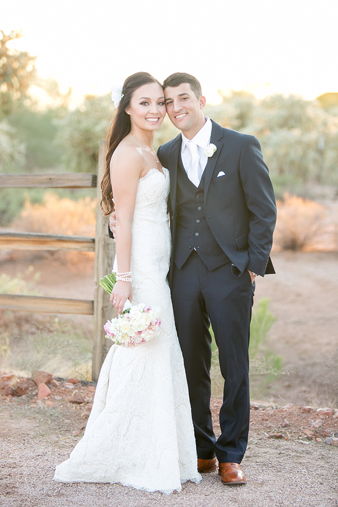 Groom in a three-piece suit  with wingtip shoes and bride in a strapless lace dress. Classic style.