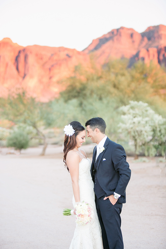 Bride & groom laugh together -- stunning backdrop of the Arizona mountains. Outdoor bridal portraits