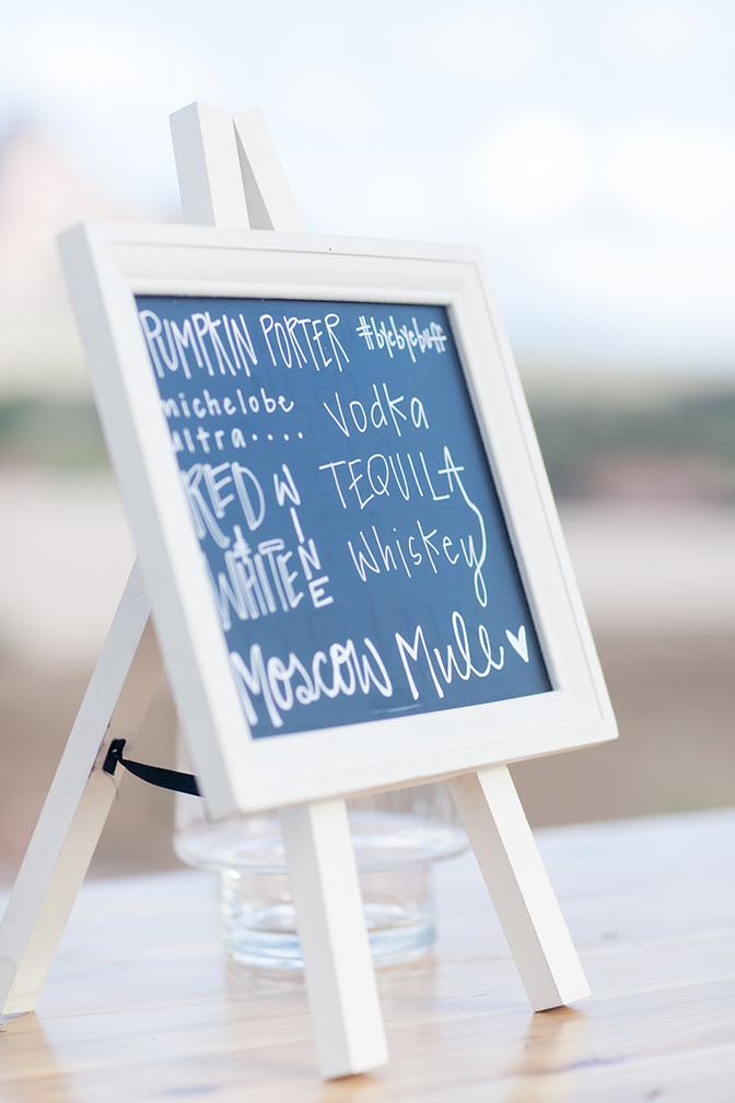 Chalkboard easel listing drink specials for the wedding reception. DIY wedding project.